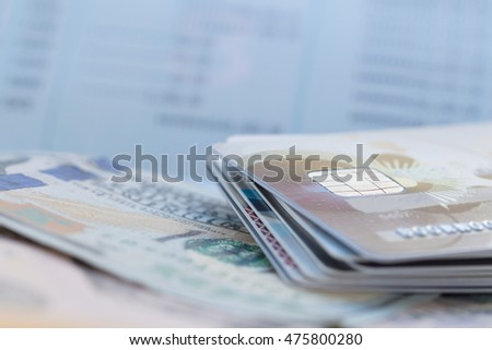 Close up credit card with pen on dollar bill over account passbook background