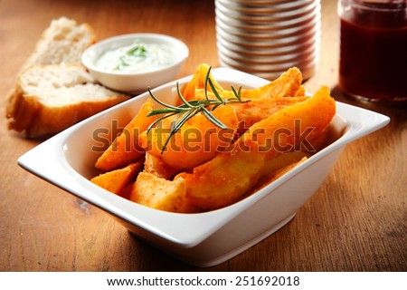 Close up Crispy Fried Potatoes on White Bowl with Herbs on Top, Placed on Wooden Table. - stock photo