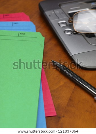 Close-up cropped image of pen and files with keyboard and spectacles on wooden office desk. - stock photo