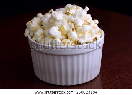 Close-up cropped image of popcorn over wood background / Cropped Popcorn in a white ceramic bowl over wood background / Close-up cropped image of popcorn over wood background (corn, pop corn, snack) - stock photo
