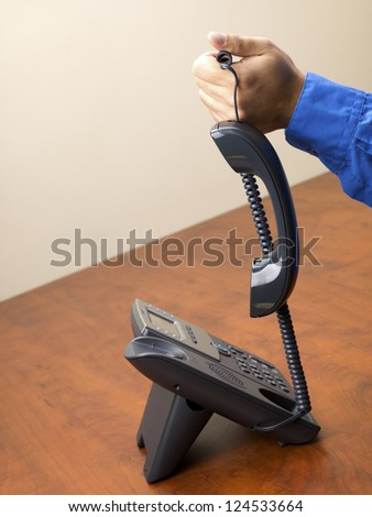 Close-up cropped shot of a man holding landline phone wire in hand. - stock photo