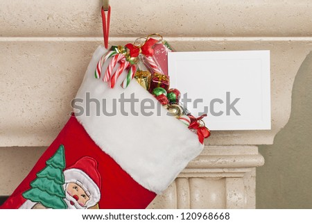 Close-up cropped view of red Christmas stocking with various candies and an empty placard. - stock photo