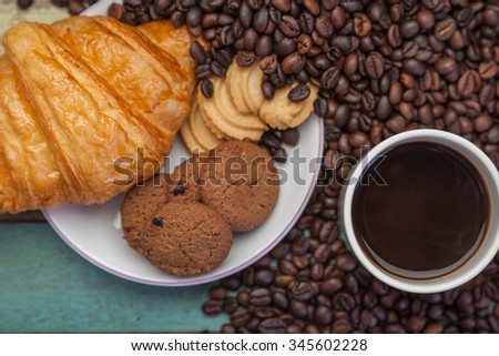 Close up cup of coffee with cookies and beans background - stock photo