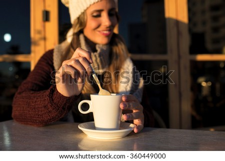 Close-up cup of coffee with woman in background - stock photo