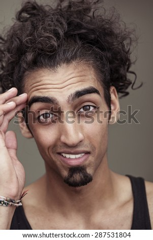 Close up Curly-Haired Young Bearded Man Smiling at the Camera with Hand Touching his Face, Isolated on Gray Background. - stock photo