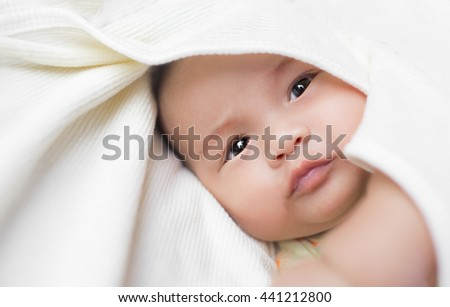 Close-up Cute Asian male baby with a towel. 3 months baby boy lying on a towel. Healthy baby boy. Blurred background. Copy space. - stock photo
