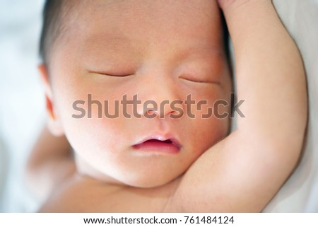 Close up cute Asian newborn baby sleeping, 7 days old.
