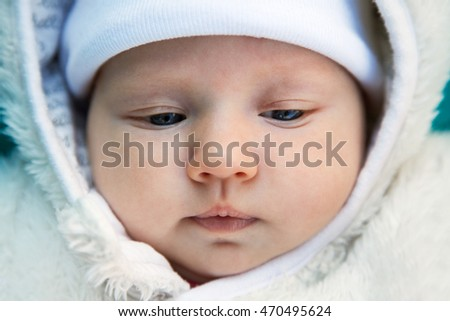 Close up cute baby's face in a white hat and hood