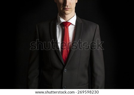 close up dark portrait of an anonymous businessman on black background - stock photo