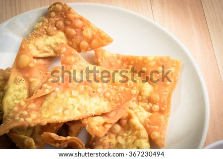 Close up Delicious Fried dumpling crispy with spicy sauce on the wood table - stock photo