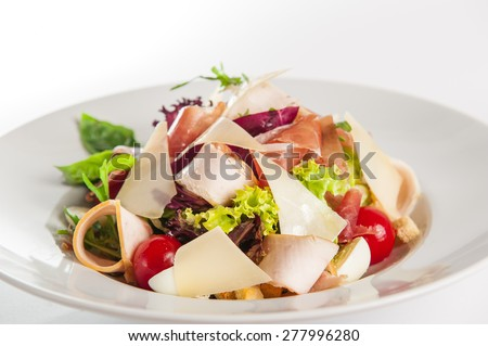 Close up Delicious Meat salad with prosciutto, ham and herbs decorated with parmesan slices, cherry and basil on a white plate isolated  - stock photo