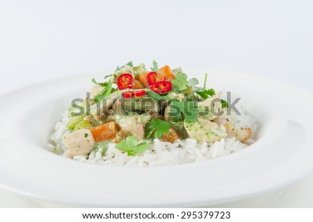 Close up Delicious portion of rice with stewed seafood and vegetables in pesto sauce decorated with parsley and paprika on the white plate isolated