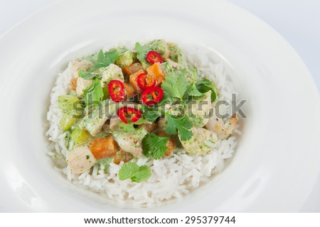 Close up Delicious portion of rice with stewed seafood and vegetables in pesto sauce decorated with parsley and paprika on the white plate isolated - stock photo