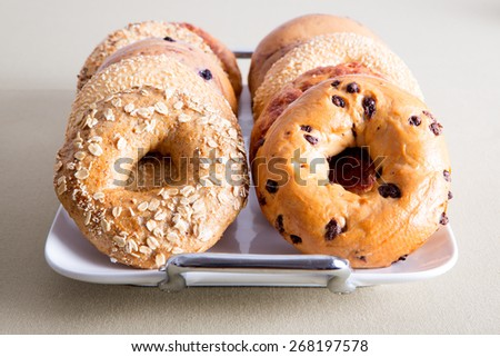 Close up Deliciously Baked Bagel Breads for Office Snacks Piled on a White Tray and Served on the Table. - stock photo