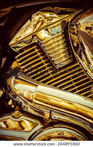 Close up detail image of shiny golden metal engine block of chopper motorcycle on the street - stock photo