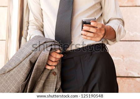 Close up detail of a businessman body section and hand holding a suit jacket and using a smart phone by an office building in the city.