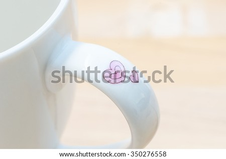 Close up detail  of a cup  handle with pink heart print.