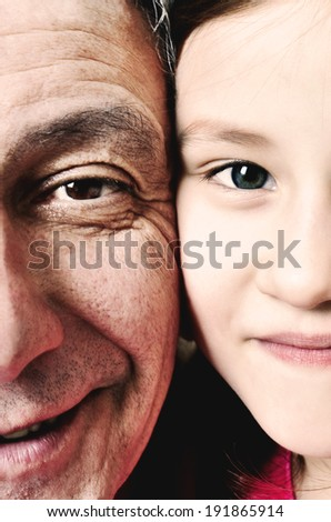 Close up detail of a little girl and her grandfather with their faces pressed close together. Young and Old/ - stock photo