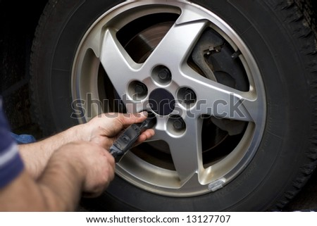 Close-up detail of a mechanic tightening or loosening the lugs of an aluminum rim.