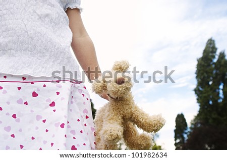 Close up detail of a soft toy held by a young girl in the park, against a blue sky. - stock photo
