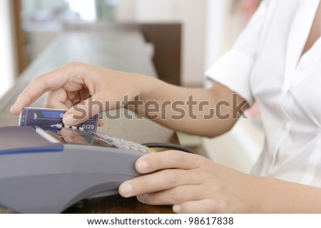 Close up detail of a store attendant's hands sweeping a credit card in a card reader.