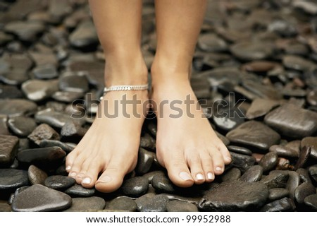 Close up detail of a woman's feet wearing an anklet and standing on black stones. - stock photo
