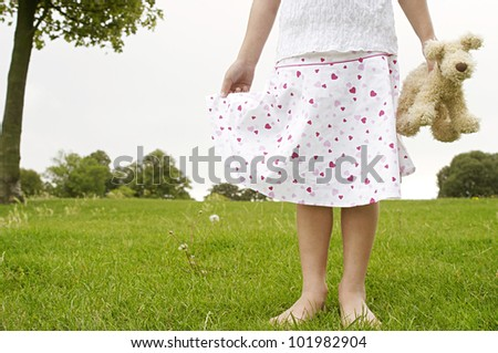 Close up detail of a young girl holding a soft toy in the park, body section. - stock photo