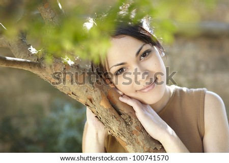 Close up detail of a young woman leaning her head on a tree in the park, smiling at camera. - stock photo