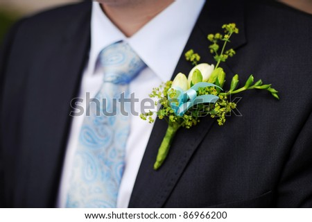 close up detail of an elegant groom's suit with a buttonhole - stock photo