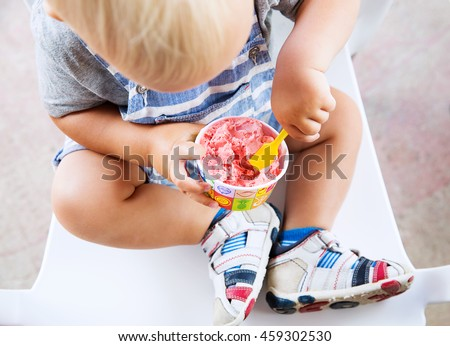 Close-up detail of child toddler eating strawberry ice cream. Outdoor at the cafe - stock photo