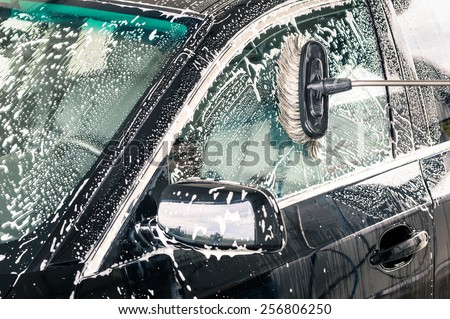 Close up detail of cleaning brush on car at carwash - stock photo