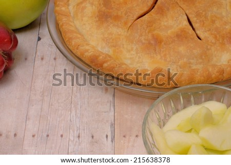 Close up detail of freshly baked apple pie with uncooked apples around on rustic wooden table. The vented crust is golden brown. Image is horizontal orientation with copy space on the table top - stock photo