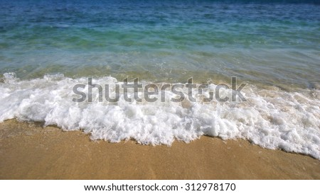 Close-up detail of the sea waves washing ashore at the beach. - stock photo
