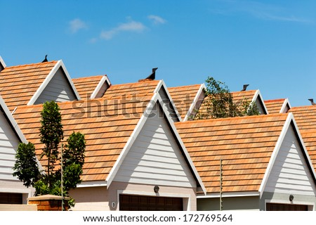 Close up detail of town house rooftops against blue sky. - stock photo