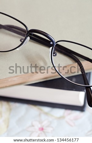 Close up detail of two books and a pair of glasses laying on top of a bed in a home bedroom.