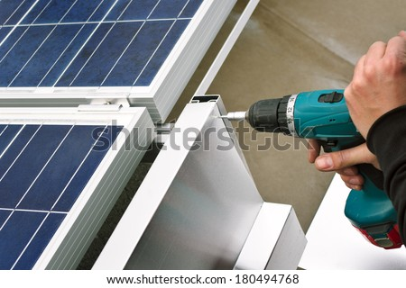Close up detail of worker with electrical drill or borer installing windbreaker on solar panel construction on a flat roof. - stock photo