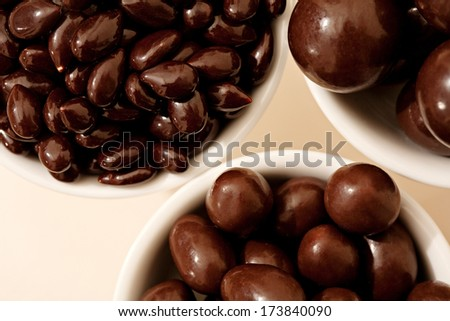 Close up detail over head view of white containers holding different sizes of dark chocolate covered nuts and fruits against a white background. Interior tempting energy sweet food.