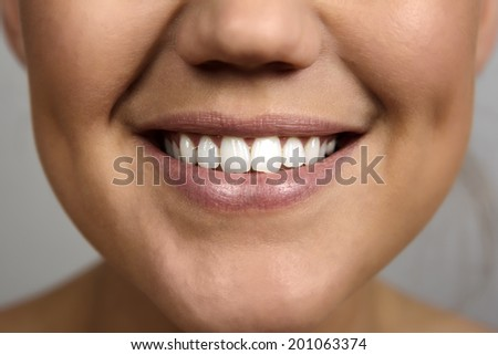 close up detail shot of a beautiful woman's mouth smiling - stock photo