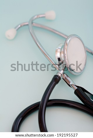 Close up detail still life view of a doctor stethoscope laying on a plain blue background in a hospital table, interior. Health and medical equipment and insurance icon with no people.