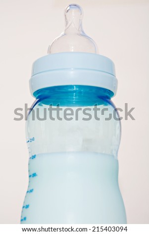 Close up detail view of a blue glass baby bottle full of warm milk standing isolated against a plain white background, indoors. Still life of a baby boy feeding bottle.