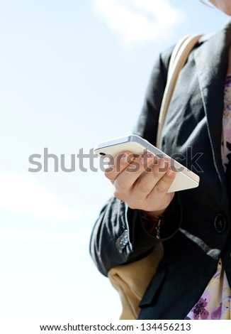 "Close up detail view of a businesswoman hand holding and using a digital ""smart phone"" while standing against a sunny blue sky."