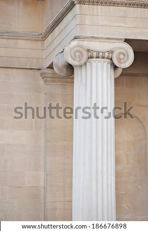 Close up detail view of a centenary old stone building exterior with a vertical decorative column and design patterns. Grand and luxurious classic architecture still life of London city, outdoors.