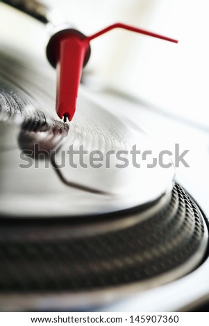 Close up detail view of a dj turntable deck and needle playing a vinyl disc with the light shining and reflections. - stock photo