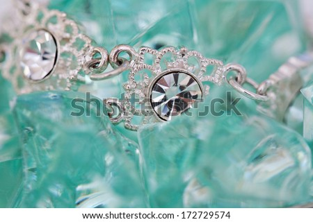 Close up detail view of a fine quality luxurious diamond necklace on a green turquoise minerals stone bed background. Diamond stones on white gold bracelet jewel and fashion accessory. - stock photo