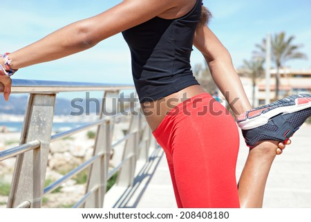 Close up detail view of a healthy woman middle body section stretching her legs while exercising by the seaside, holding and pulling her muscles during a sport training day. Sporty lifestyle outdoors. - stock photo