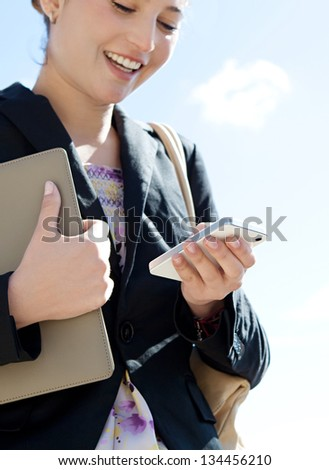 Close up detail view of a joyful businesswoman holding in her hand and using a smartphone while standing against a sunny blue sky.