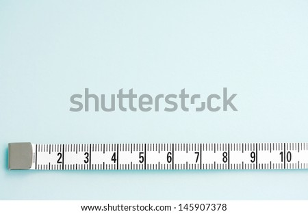 Close up detail view of a measuring tape stretched in a straight line isolated on a clean blue background. - stock photo