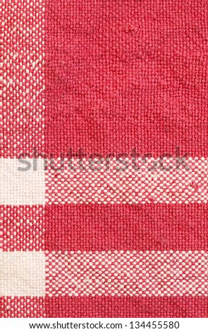 Close up detail view of a patterned cotton kitchen cloth with visible weave and bright red color checks. - stock photo