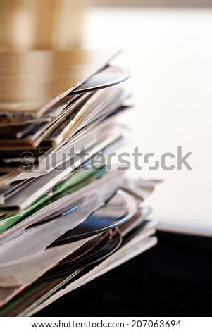 Close up detail view of a pile of old and used vinyl records in a night club interior. Music and sound interests collection. - stock photo