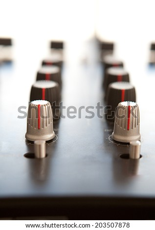 Close up detail view of a professional DJ mixing deck with multiple buttons and controls against a bright light, interior. Night club and techno music quality equipment. - stock photo